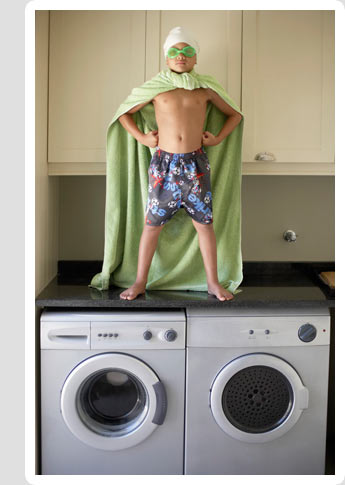 Super-hero child standing on washer & dryer
